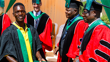 School of Agriculture for Family Independence (SAFI) students in their graduation gowns receive their diplomas.