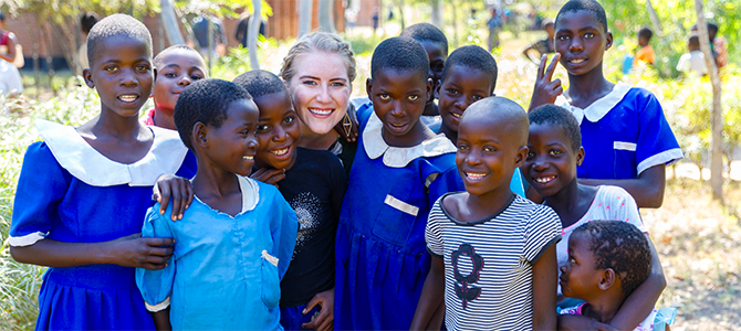 Nu Skin Employee Emily Sander poses for a picture with a group of children from Malawi.