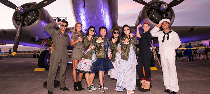 Nu Skin Sales Leaders pose in front of airplane on Ford Island dressed in military themed attire.