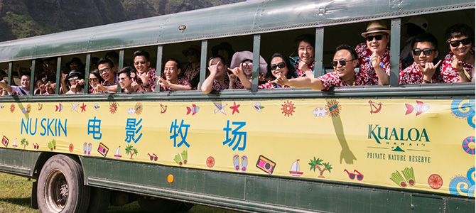A group of Nu Skin Sales Leaders from Greater China pose for a picture while inside a garden car.