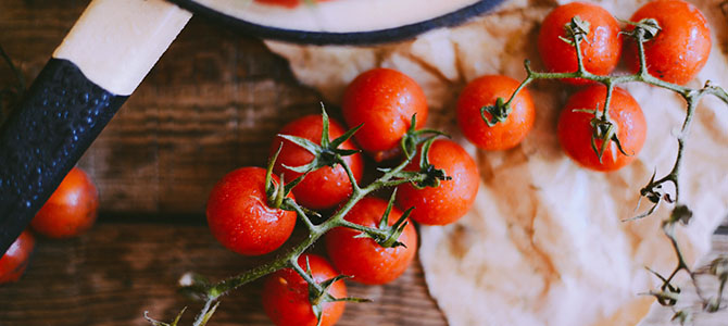 Fresh tomatoes on a vine spread out across a countertop.